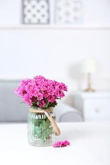 Bellissimi fiori in vaso sul tavolo in camera