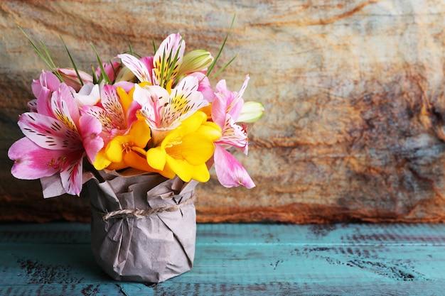 Bellissimi fiori in vaso su legno