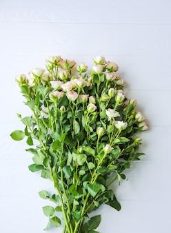 Bellissimi fiori su sfondo bianco. mazzo di rose. posa piatta perfetta. cartolina di festa della madre felice. saluto per la giornata internazionale della donna. idea elegante per pubblicità o promozione.