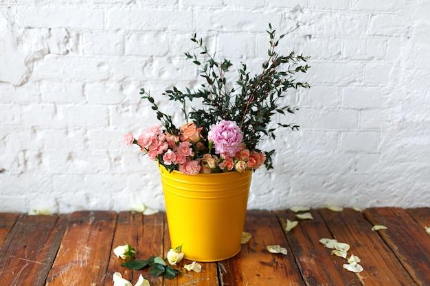 Bellissimi fiori in un vaso giallo sul muro di mattoni bianchi