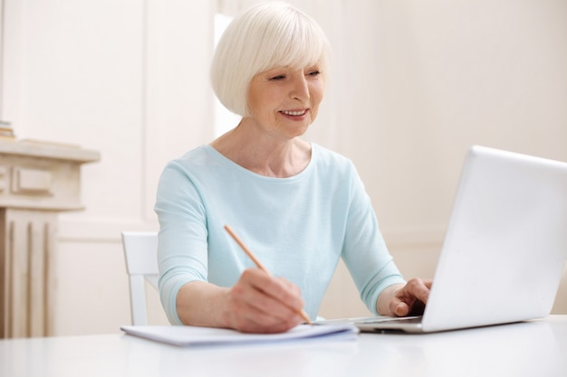 Bella donna anziana concentrata che trova consigli utili online e li scrive usando la matita