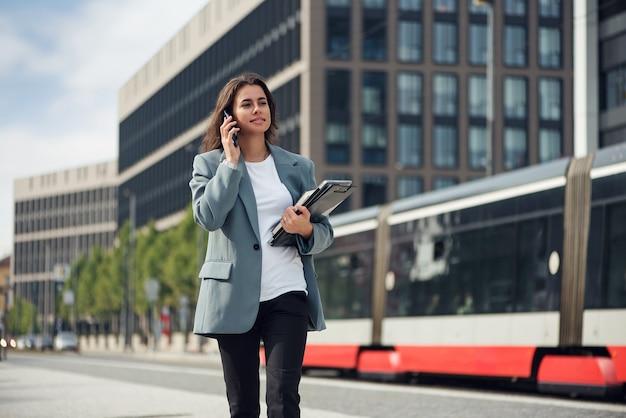 Bella donna d'affari vestita formale in tuta con un laptop e un notebook bruna all'aperto