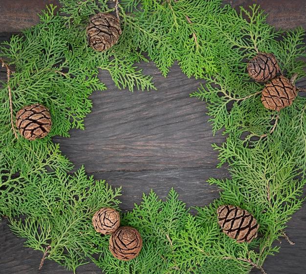 Bella cornice da rami di thuja dell'albero di natale e coni. ghirlanda di natale sulla tavola di legno scuro. copia spazio