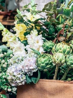 Bellissimi carciofi verdi decorativi freschi e altri fiori nel piccolo fioraio