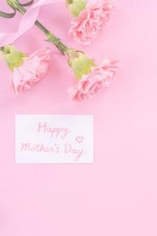 Bello, fresco ed elegante bouquet di fiori di garofano con biglietto di auguri di ringraziamento bianco isolato su sfondo di colore rosa brillante, vista dall'alto, concetto di disposizione piatta.