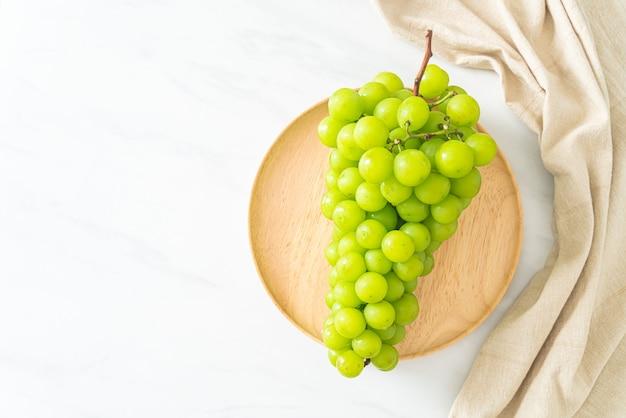 Bella e fresca uva verde su piatto di legno