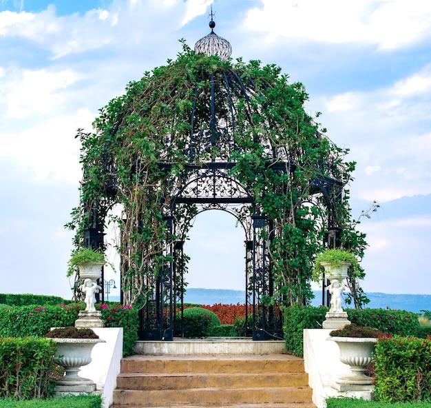Bellissimo padiglione naturale fresco fatto di acciaio e piante verdi, paesaggio nel parco
