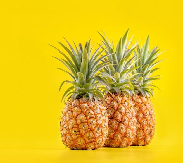 Bellissimo ananas fresco isolato su sfondo giallo brillante, concetto di modello di idea di progettazione di frutta stagionale estiva, spazio di copia, da vicino