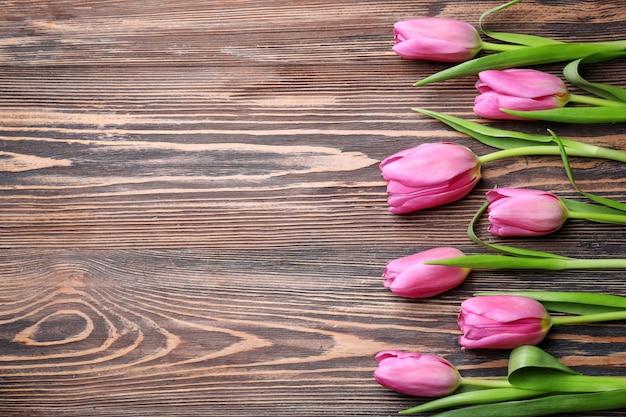 Bellissimi tulipani freschi su fondo in legno