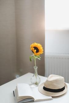 Bellissimo girasole giallo fresco, cappello di paglia e un libro su un tavolo vicino a una finestra con tende