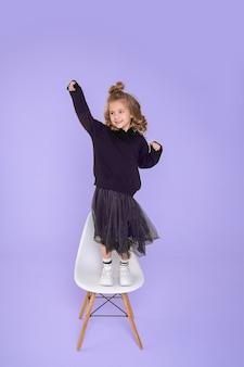 Bella ragazza divertente 6-7 anni sta ballando sulla sedia in studio su sfondo viola. concetto di gioia della vittoria, sorpresa. foto a figura intera