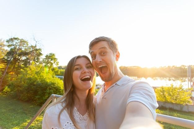 Bella coppia romantica divertente sullo sfondo della natura. attraente giovane donna e bell'uomo stanno facendo selfie, sorridendo e guardando la fotocamera.