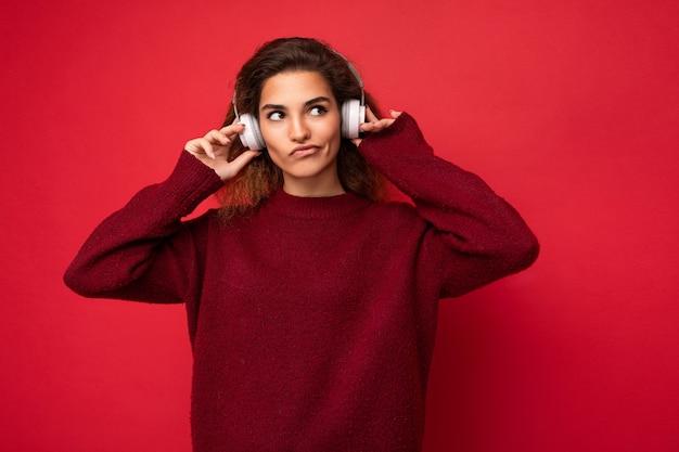 Bella divertente premurosa giovane donna riccia bruna che indossa un maglione rosso scuro isolato