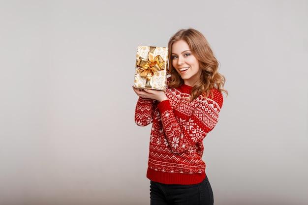Bella donna divertente in un maglione lavorato a maglia rosso con una stampa che tiene un regalo Foto Premium