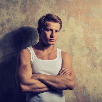 Bello gay in maglietta bianca che posa contro lo spazio del grunge