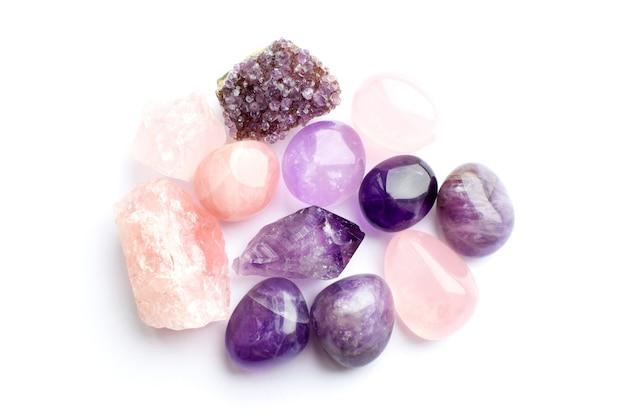Belle pietre preziose e drusi di ametista minerale viola naturale su sfondo bianco. ametiste e quarzo rosa. grandi cristalli di pietre semipreziose.