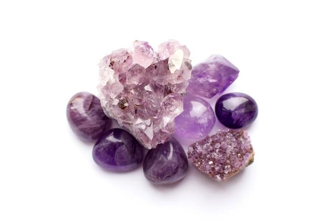 Belle pietre preziose e drusi di ametista minerale viola naturale su sfondo bianco. grandi cristalli di pietre semipreziose.