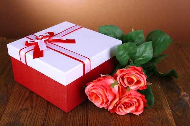 Bella confezione regalo con fiori sul tavolo su superficie marrone