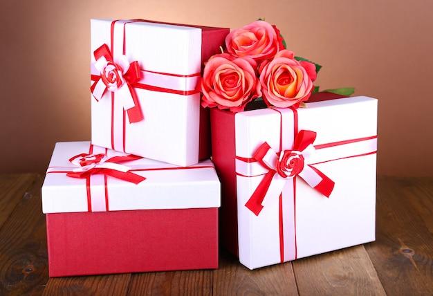 Bellissime scatole regalo con fiori sul tavolo su sfondo marrone