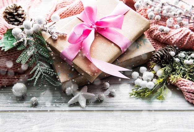 Bellissimi regali per natale con decorazioni su una superficie di legno