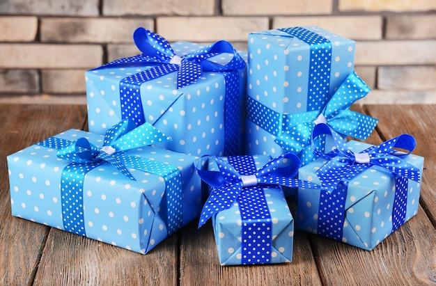 Bellissimi regali sul tavolo sullo sfondo del muro di mattoni