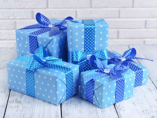 Bellissimi regali sul tavolo sulla superficie del muro di mattoni