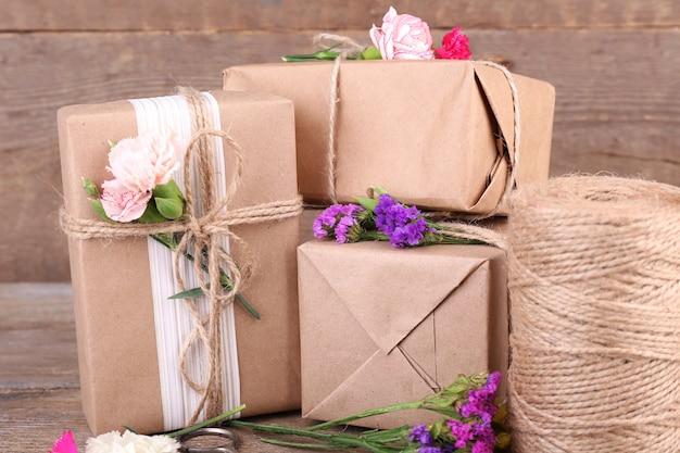 Bellissimi regali con fiori e corda decorativa, su una vecchia superficie in legno