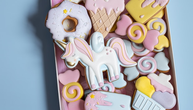 Bellissimi biscotti di panpepato per la festa dei bambini a forma di unicorno e dolci, piatti distesi.