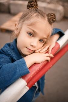 Una bella ragazza di circa sette anni con una giacca di jeans sta guardando la telecamera
