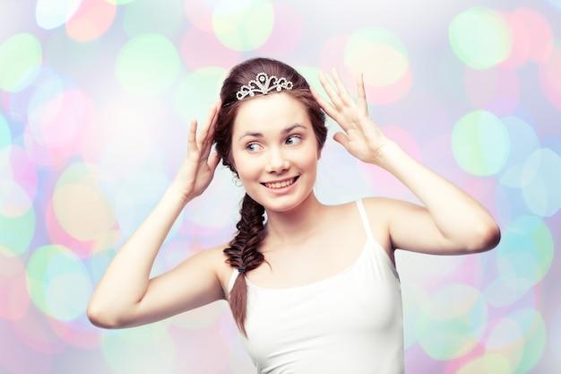 Bella ragazza che ammira la sua tiara di diamanti