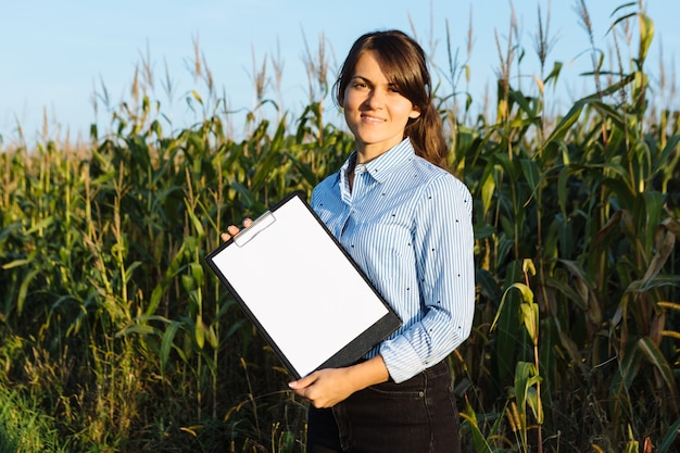 Bella ragazza agronoma con taccuino e analizza il raccolto di mais