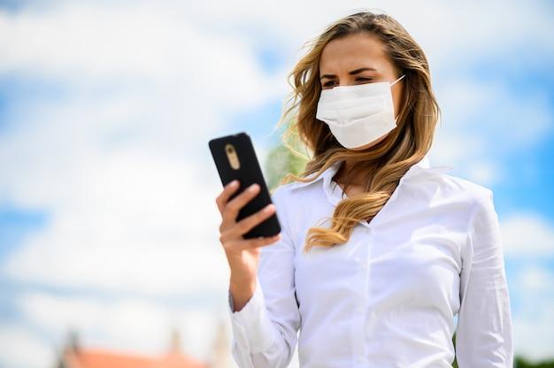 Bella ragazza da sola giovane donna che utilizza il suo smartphone e indossa una maschera, concetto di coronavirus