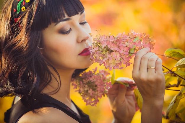Bella ragazza di aspetto asiatico in autunno nei fiori profumati del parco