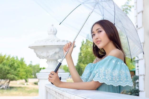 La bella ragazza dell'aspetto asiatico sta stando con l'ombrello trasparente