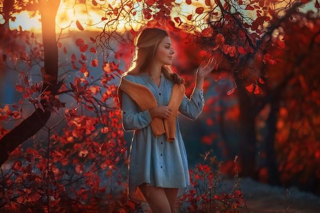 Bella ragazza nel giardino di autunno in alberi con foglie gialle rosse