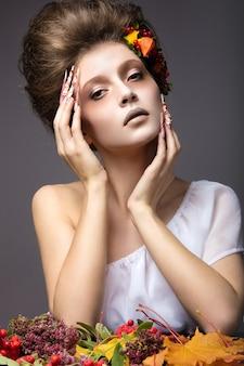 Bella ragazza in immagine autunnale con unghie lunghe con trucco luminoso e insolito. foto scattata in studio su sfondo grigio