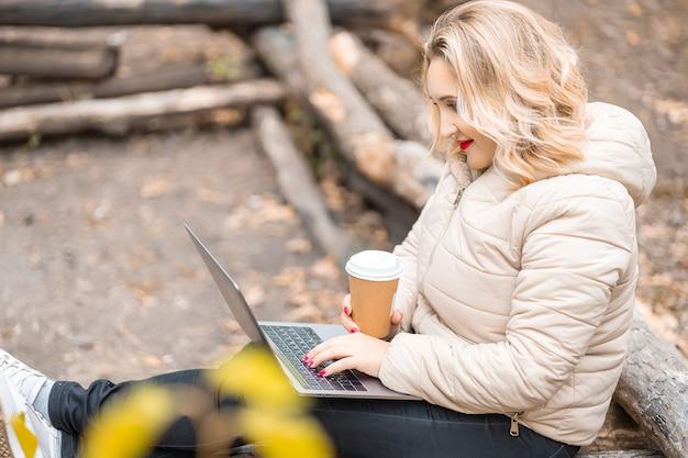 Una bella ragazza in un parco autunnale tiene in mano un bicchiere di caffè usa e getta e lavora su un laptop