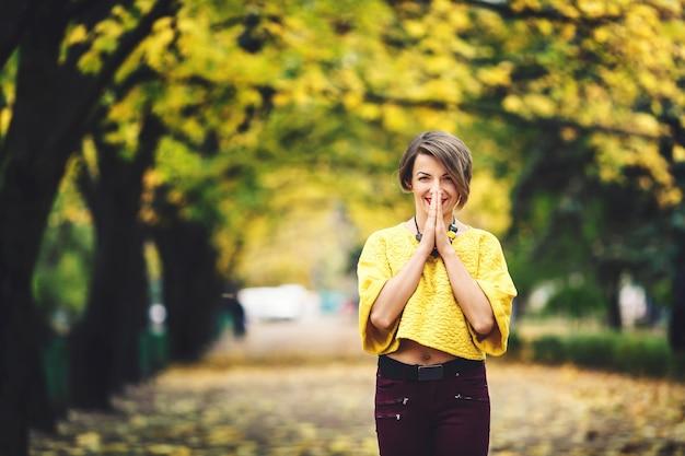 La bella ragazza in autunno si leva in piedi sul vicolo con gli aceri gialli e tiene le sue mani vicino alla sua bocca con il sorriso.