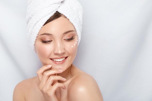 Bella ragazza in telo da bagno con crema sotto gli occhi toccando il suo viso e guardando in basso a lato
