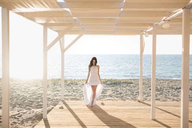 Bella ragazza sulla spiaggia in abito bianco.