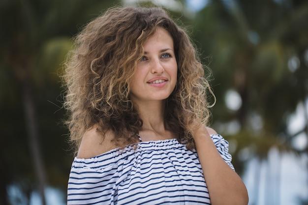 Bella ragazza sulla spiaggia con palme