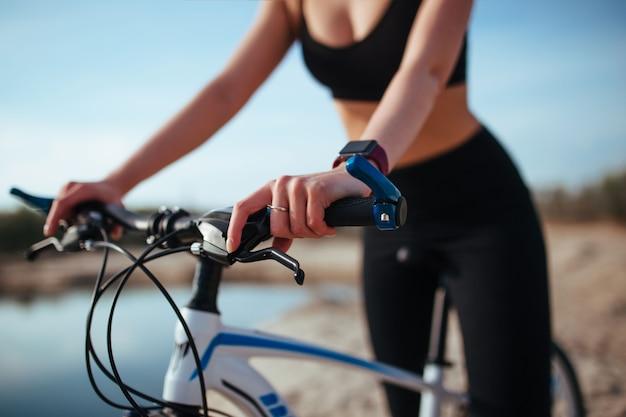 Bella ragazza in bicicletta sulla sabbia vicino al fiume