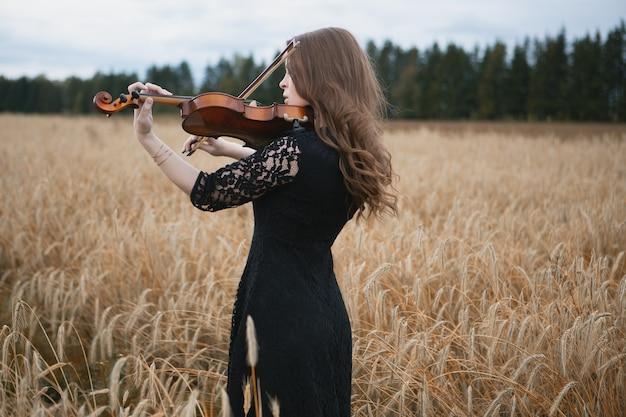 Bella ragazza in un vestito nero suona il violino in un campo di grano