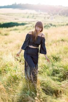 Bella ragazza in abito nero che cammina e sorride all'aperto in un prato durante il tramonto estivo
