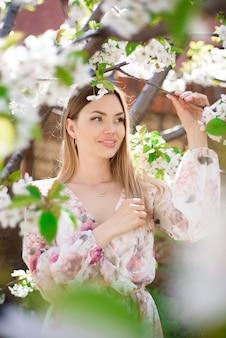 Una bella ragazza in un giardino primaverile in fiore.