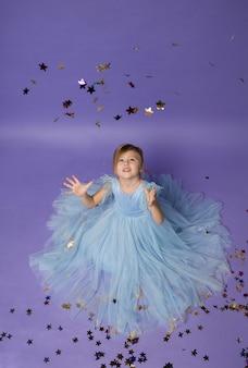 Una bella ragazza in un vestito blu cattura i coriandoli con le mani sul viola