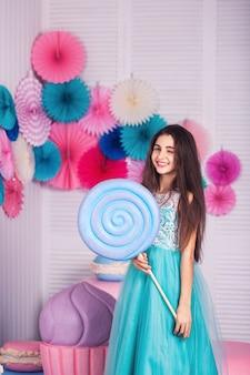 Bella ragazza in vestito blu tenere in mano enormi caramelle in studio con decorazioni di amaretti. copia spazio.