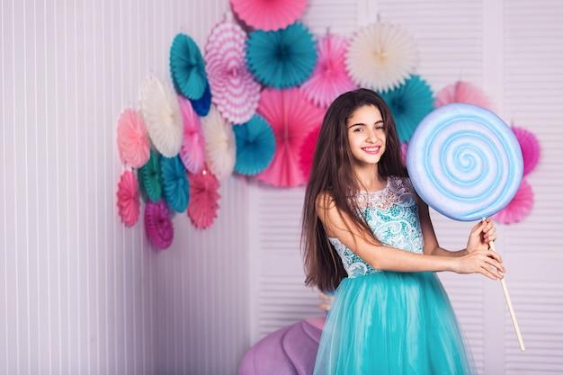 Bella ragazza in abito blu tenere in mano enormi caramelle con decorazioni di amaretti