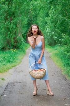 Una bella ragazza in un vestito blu con un cesto in mano si trova sulla strada nel parco.