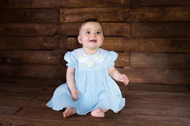 Bella ragazza in abito blu su sfondo di legno